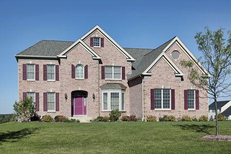 Brick home in suburbs with pink door photo