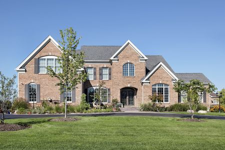 Large luxury brick home with arched entry photo