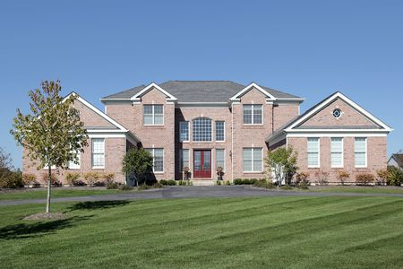 Large brick home in suburbs with red door photo