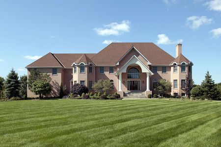 Large brick luxury home with arched entry photo