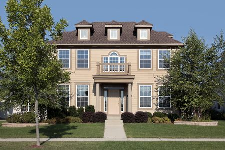 Salmon colored suburban home with front balcony photo