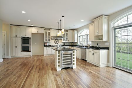 wooden floors: Kitchen in new construction home with white cabinetry
