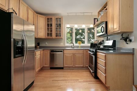 appliances: Kitchen in luxury home with oak cabinetry Stock Photo
