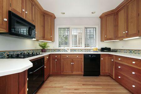 Keuken in huis in de voorsteden met cabinetry kersenhout