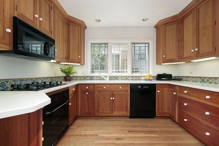 Kitchen in suburban home with cherry wood cabinetry Stock Photo