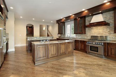 Kitchen in new construction home with cherry wood cabinets photo