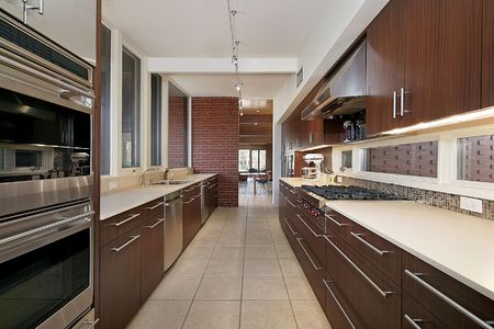 kitchen furniture: Kitchen in suburban home with dark wood cabinetry