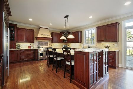 lighting fixtures: Kitchen in luxury home with cherry wood cabinetry Stock Photo