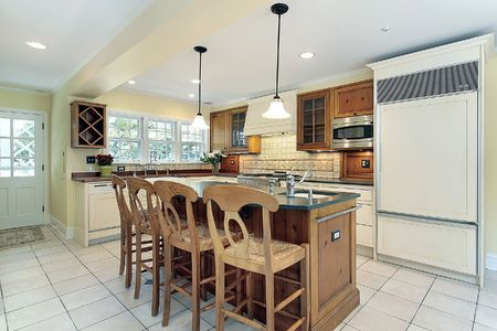 Kitchen in suburban home with white tile flooring photo