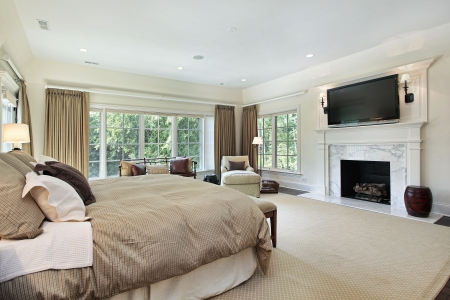 Master bedroom in luxury home with marble fireplace photo