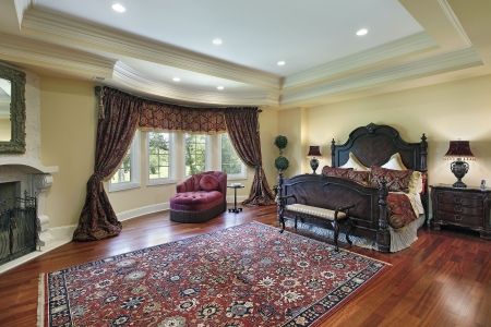 recessed: Luxury master bedroom with recessed ceiling and fireplace