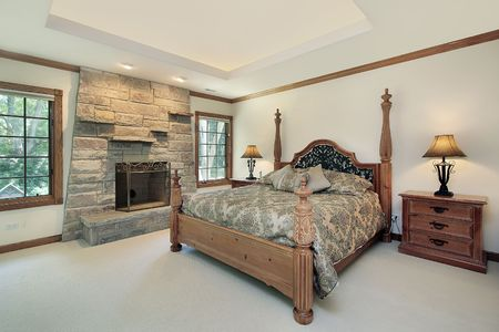 Master bedroom in luxury home with stone fireplace photo