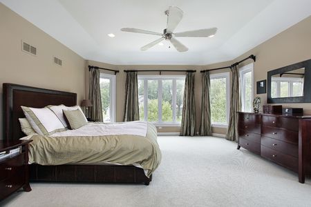 Master bedroom in luxury home with wall of windows