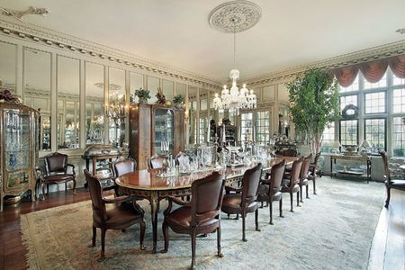 dining table and chairs: Formal dining room in traditional home with wall mirrors