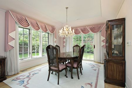 Traditional dining room in suburban home with pink draperies photo