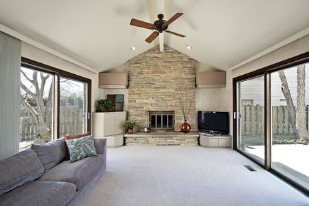 Family room with stone fireplace and two sliding doors Stock Photo