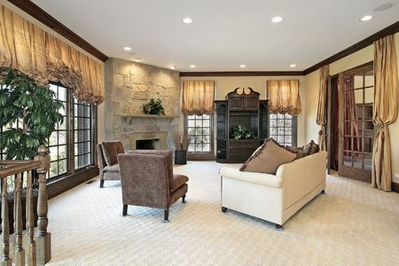 Family room in luxury home with stone fireplace photo