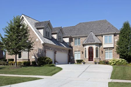 Brick home with red wood door and three car garage photo