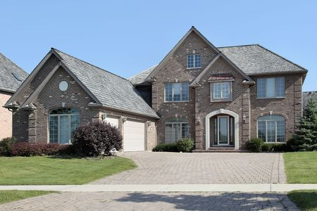 Suburban brick home with arched entry and three car garage photo