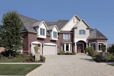 Luxury suburban brick home with stone pillars photo