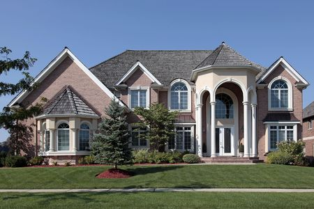 Large brick home in suburbs with columned entryway photo