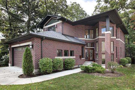Luxe bakstenen huis in voorsteden met glazen voordeur Stockfoto
