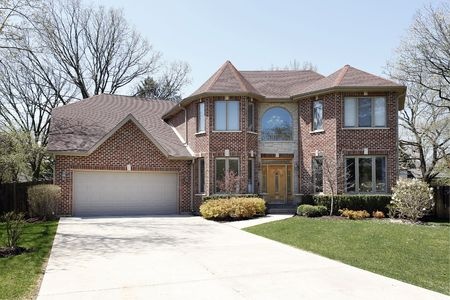 custom house: Luxury brick home in suburbs with stone entryway