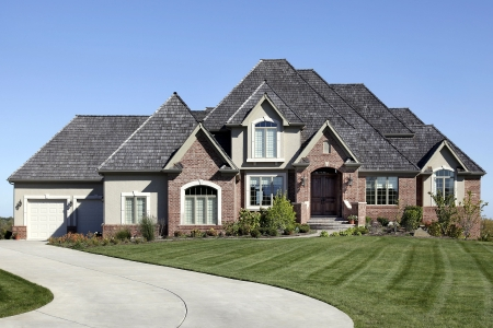 Luxury brick home with cedar shake roof photo