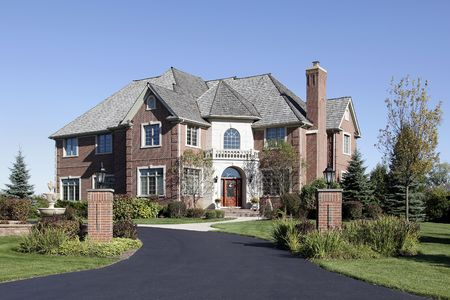 driveways: Luxury brick home in suburbs with front balcony