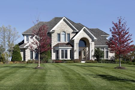wood lawn: Luxury suburban home with arched entry and cedar roof Stock Photo