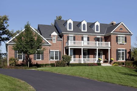 Luxury brick home with front balcony and porch photo