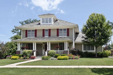 Suburban home with front porch and red shutters photo