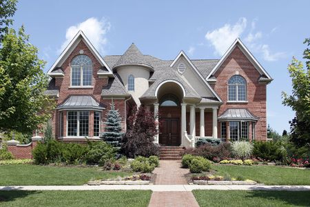 Luxury brick home with turret and arched entry photo