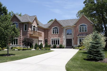 Large luxury brick home with front balcony photo