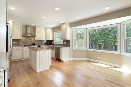 wood floor: Kitchen in remodeled home with large picture window