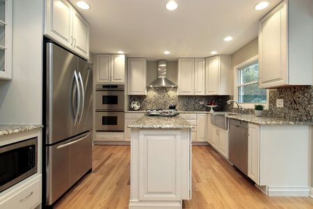 island: Kitchen in suburban home with light colored cabinetry