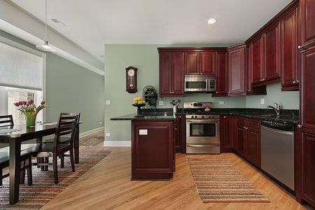 kitchen furniture: Kitchen in condominium with cherry wood cabinetry