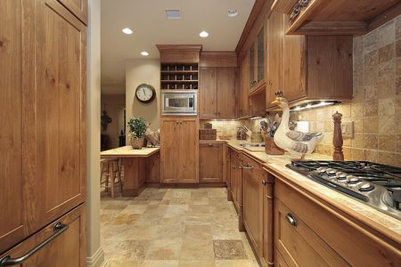 wood floor: Country kitchen in condominium with oak cabinetry