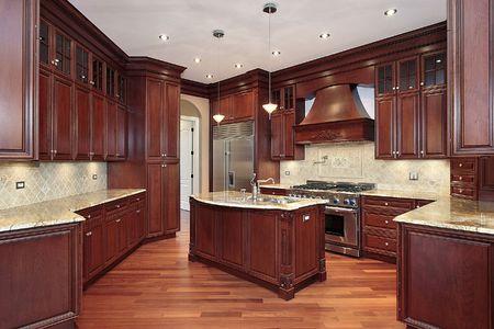 Keuken in nieuwbouw huis met kersen houten kasten Stockfoto