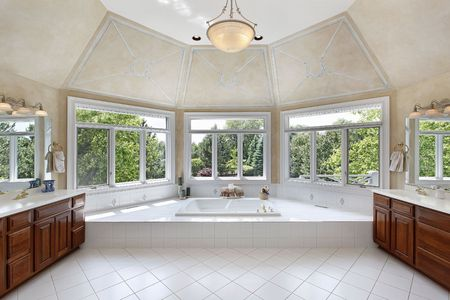 Master bath in luxury home with windowed tub area photo
