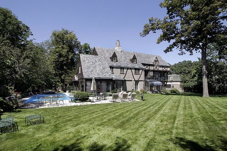 Luxury home with large lawn and swimming pool photo