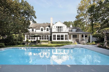 Rear view of luxury home with large swimming pool photo