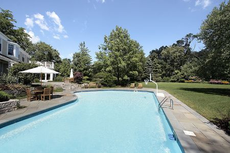 Luxury home with large swimming pool and deck photo