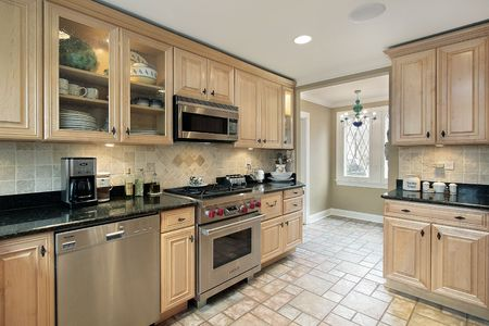 tile floor: Kitchen in suburban home with oak cabinetry