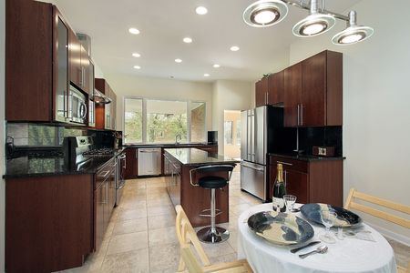 Kitchen in remodeled home with dark wood cabinetry photo