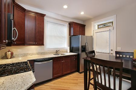 Kitchen in condominium with cherry wood cabinetry photo