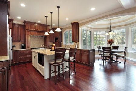 Kitchen with eating area and cherry wood flooring photo