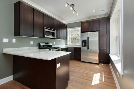 cucina moderna: Cucina in condominio ritoccata unit� mogano cabinetry