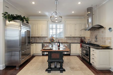 Kitchen in luxury home with cream colored cabinetry photo