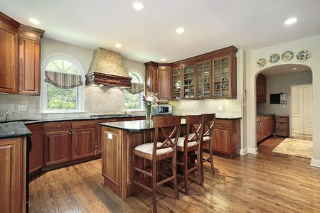 dining table and chairs: Kitchen in luxury home with cherry wood cabinetry Stock Photo